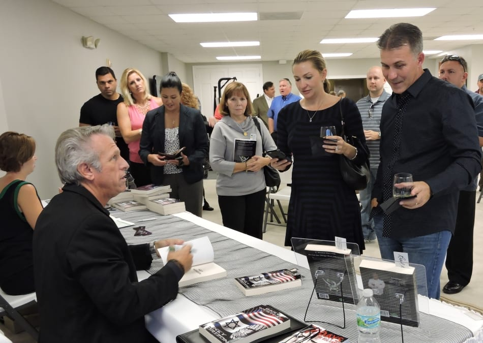 Gary signing books at a book launch. People lined up to get their book.