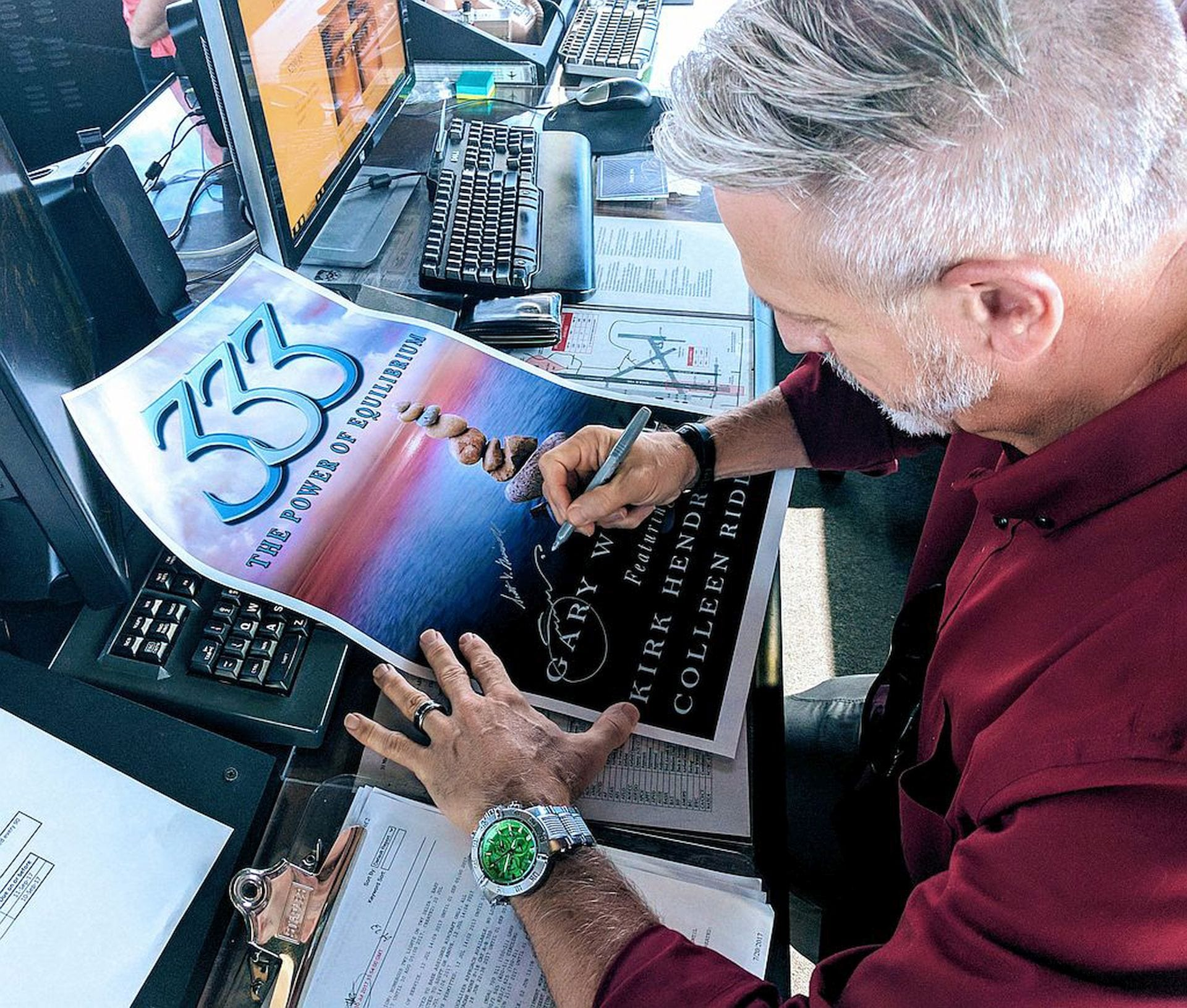 Gary signing a poster for his book: 333