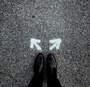 Feet, firmly planted on the pavement with two arrows, one pointing to the right and the other to the left.