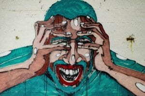 Painting of a man with his hands covering his eyes, indicating stress