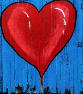 A heart painting on a wooden fence