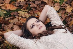 Brunette woman laying on a bed of colorful leaves looking into the sky above.