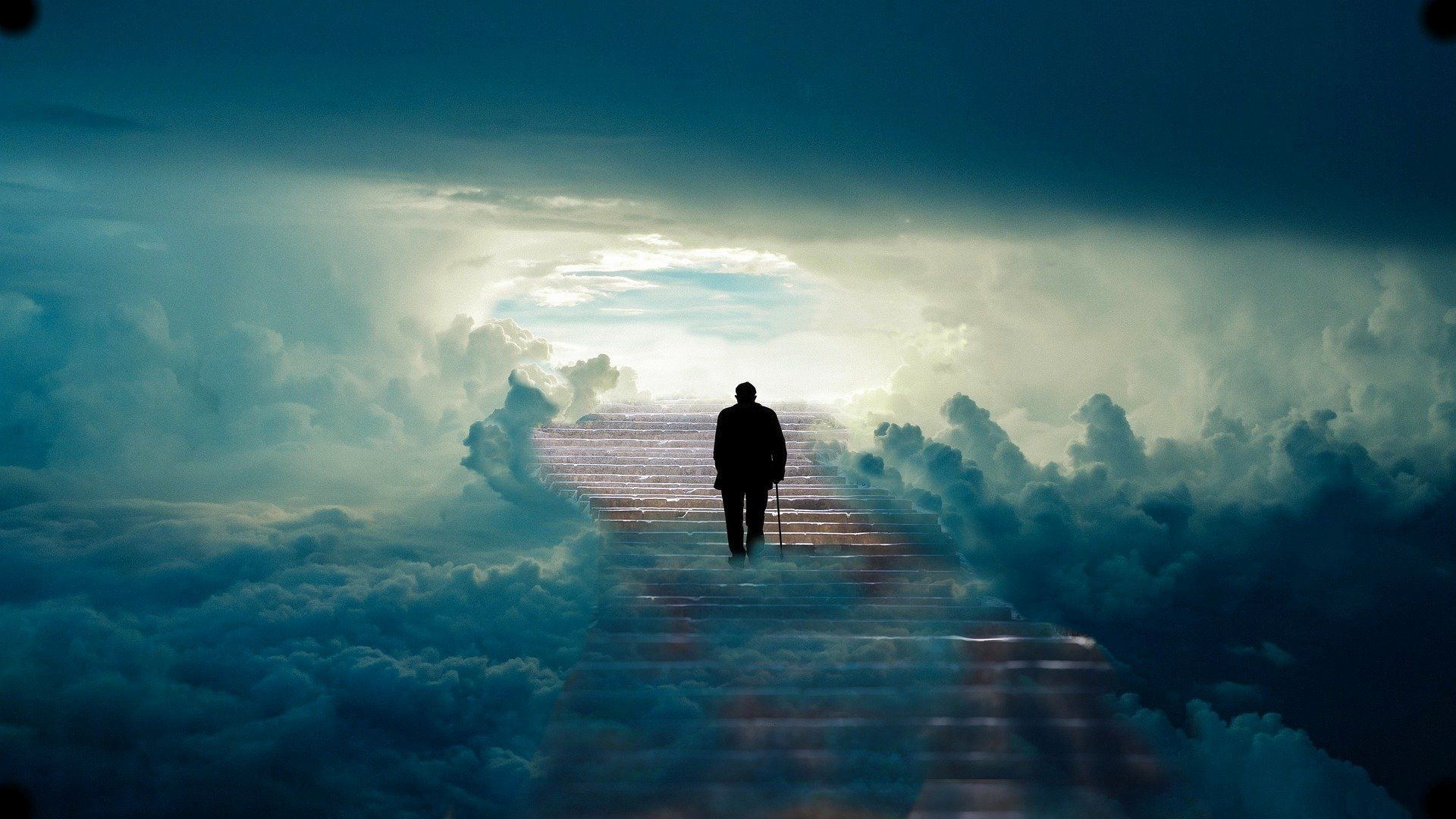 Silhouette of a man walking on a path through the clouds